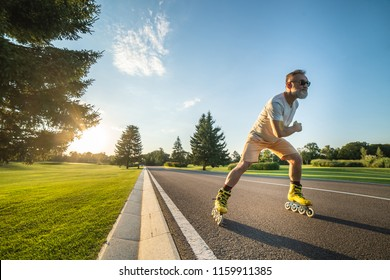 The old man in sunglasses rollerblading on the road