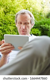 Old man with tablet computer and headphones watches a movie