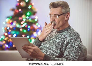 The old man with a tablet make a video call near the christmas tree