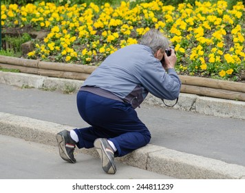 old man taking picture of yellow flowers on knees