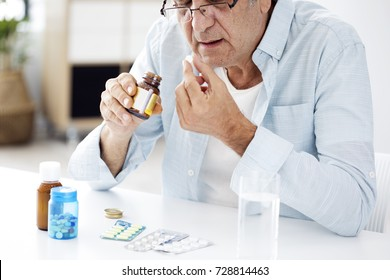 Old man taking a pill