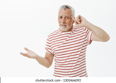 Old man things teenagers lost mind, insane. Confused and displeased senior bearded male in striped t-shirt rolling finger on temple from disappointment raising palms clueless reacting to dumb action