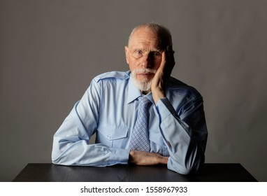 Old man in thoughts. Portrait of a bearded old man. Senior man is sitting.