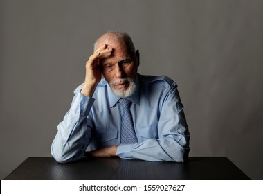 Old man in thoughts. Portrait of a bearded old man. Senior man is sitting. Grief and disease concept.