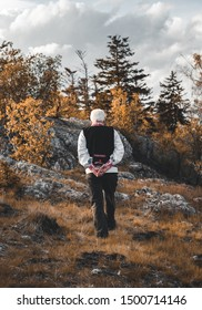 Old man in traditional Slovak national folk costume walking through the forest (mountains) with rocks, trees and cloudy sky on background.