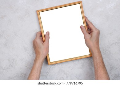 The old man tries to hang a wooden frame with a photograph on the wall. Concept studio shot. Picture isolated on white with patch.