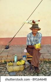 old man in trinidad, cuba, with chicken on head
