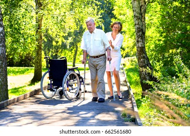 old man trying to walk with crutches and young female medical assistant in the park
