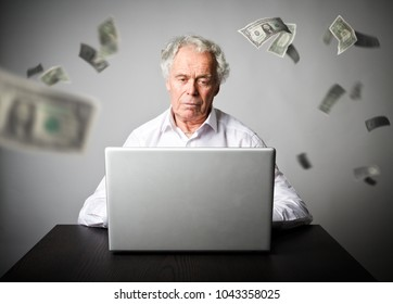 Old man is using a laptop to browse the net. Old man in white earns money on the internet. Working at home.