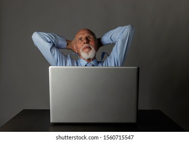 Old man is using a laptop to browse the net. Successful businessman is dreaming.Businessman finished big project. Successful business concept.
