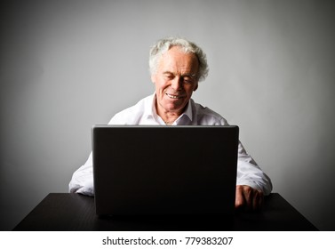Old man is using a laptop to browse the net.