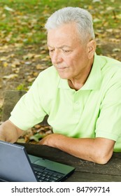Old man using laptop on the park bench.