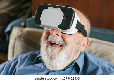 old man using virtual reality goggles at home