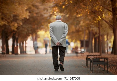 Old man walking in the autumn park.