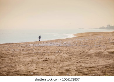old man walking away on a deserted beach