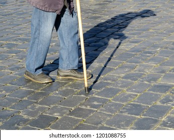 Old man walking with a cane, long shadow on pavement. Concept for old age, poverty, diseases of the spine, elderly people