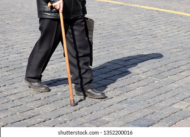 Old man walking with a cane on a street. Concept for disability, old age, limping person, diseases of the spine, elderly people