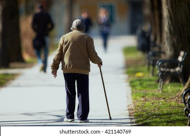 Old man walking down the street with walking stick