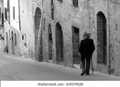 Old man walking down the street in a medieval town of Tuscany