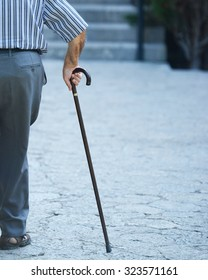 Old man walking with his hands on a wooden walking stick