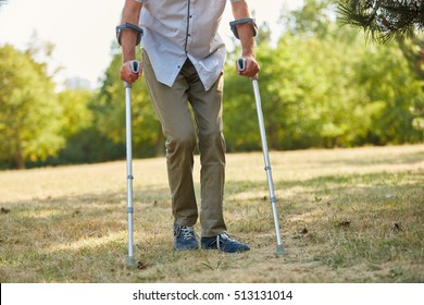 Old man walking on crutches in the nature in rehab