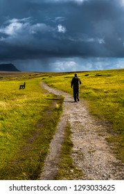 Old Man With Walking Stick Strolls On Narrow Gravel Path Through Scenic Landscape With Spectacular Clouds