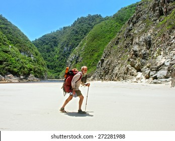 Old man walks on beach with a backpack. Shot on the Otter trail in the Tsitsikamma National Park, Garden Route area, Western Cape, South Africa.
