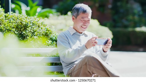 old man watch video or play mobile game by smart phone happily outdoor
