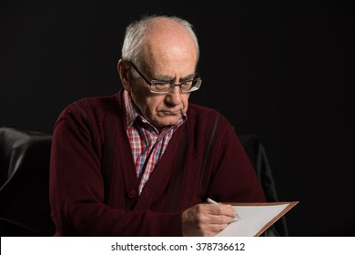 old man wearing eyeglasses writing some notices with pan and white paper