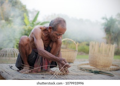 Old man are weaving in field of Thailand.