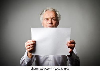 Old man in white is holding white paper in his hands.