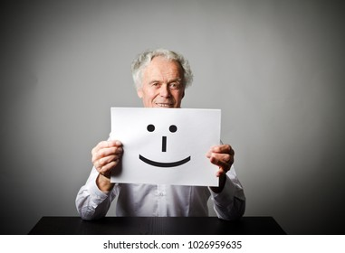 Old man in white is holding white paper with smile. Happy and smile concept.