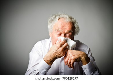 Old man in white is sneezing. Runny nose.