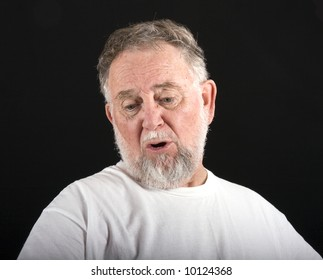 An old man in a white tshirt against a black background with an expression of woe or sadness