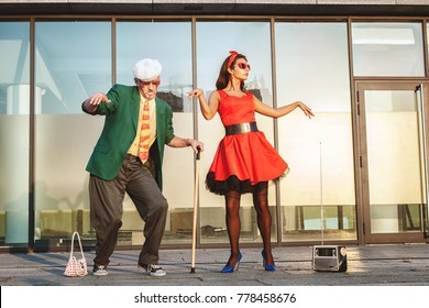 An old man and a woman dancing in the street is a fast dance, the grandfather is leaning on a cane for walking.
