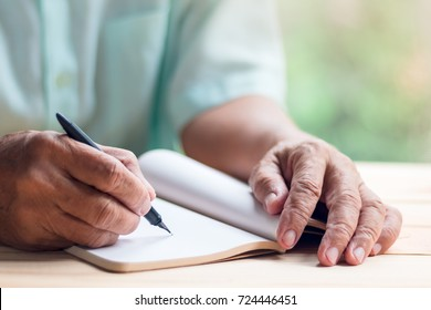 old man write on blank notebook page with black ink pen