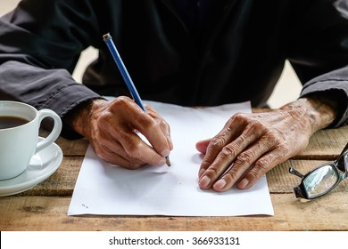 old man writing with a pencil in a notebook,Handwriting