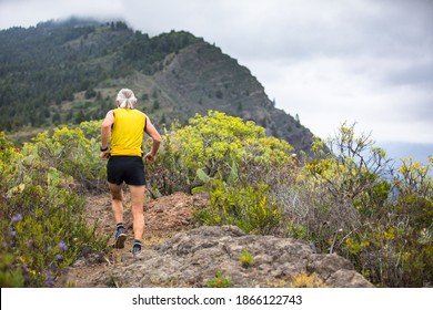 Old man in yellow t-shirt running on the trail to the mountains of canary island la palma