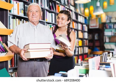 Old man with young woman are showing what they bought in bookstore.