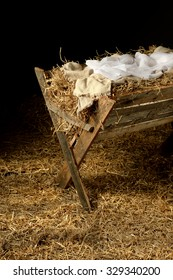 Old manger with swaddling clothes over dark background