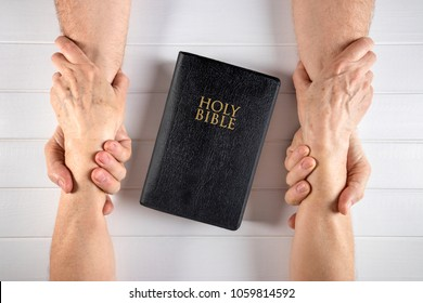 Old man/husband and woman/wife holding hands around a Holy Bible on white wood board