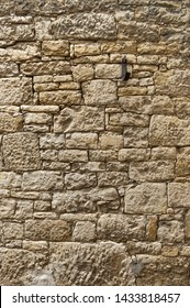 Old manicured sandstone wall of yellow sandstone with irregularly large and very small stones