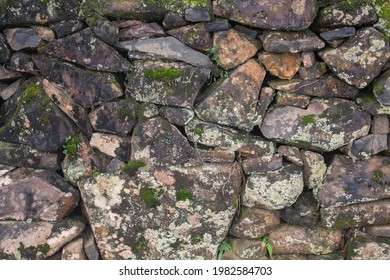An old manmade stone wall with moss on it.