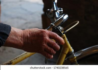 old man's hand and bike