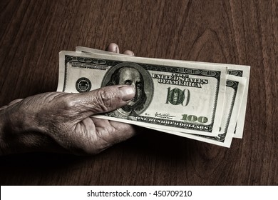 old man's hand with a hundred dollar bill