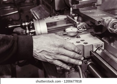 Old mans hand on an old lathe machine. Close view. Black white.