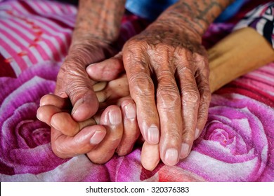The old man's hand touching the hand of a sick old woman on the bed.