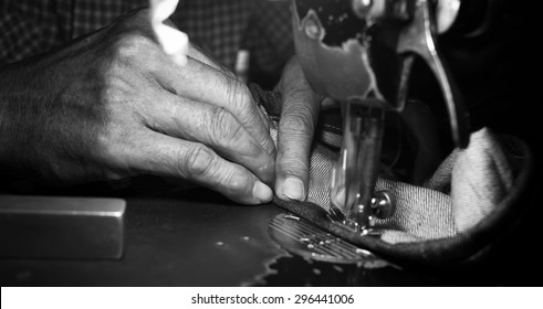 Old man's hands behind his sewing (black and white picture)