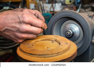 Old man's  hands with tool and grinding machine with diamond wheel. Close view.
