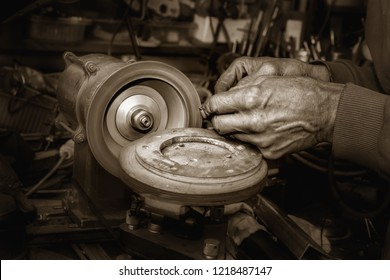 Old man's  hands with tool and grinding machine with diamond wheel. Close view. Mono color.